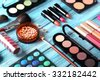 Makeup brush and cosmetics on blue wooden table - stock photo