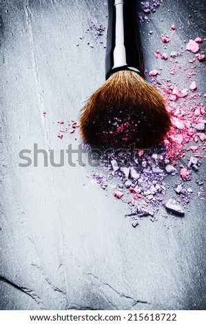 Makeup brush and crushed eyeshadows on dark background - stock photo