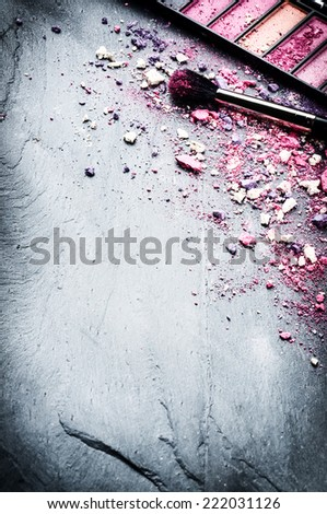 Makeup brush and crushed eyeshadows on stone background - stock photo