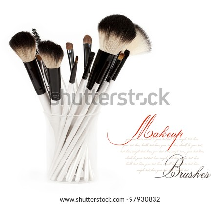 makeup brush set in a glass beaker isolated on white background - stock photo