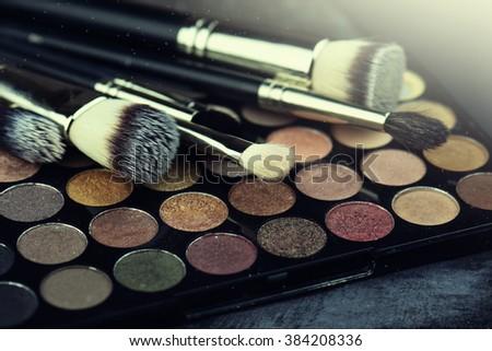 Makeup brushes and make-up eye shadows - stock photo