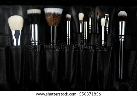 makeup brushes on a black leather background