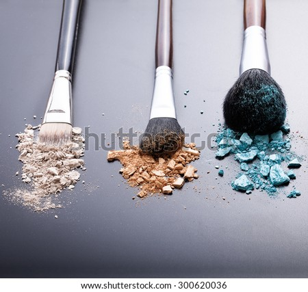 Makeup brushes on background with colorful powder.  - stock photo