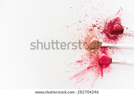 Makeup Brushes on White Background with Colorful Pigment Powder - stock photo