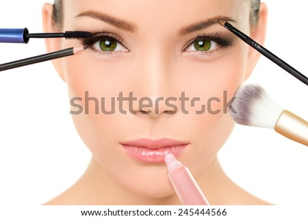 Makeup concept - Asian woman with many brushes against beauty face putting mascara, blush and lip gloss - stock photo