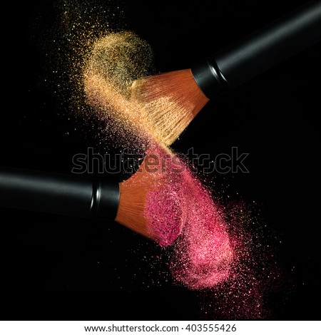 Makeup concept. Stop action view of two makeup brushes applying matching red and gold powder over black background - stock photo