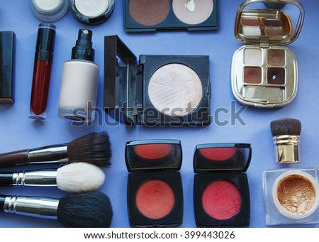 Makeup cosmetics. Brushes, blush, shadow, lipstick and other cosmetic accessories on blue background. Bright picture - stock photo