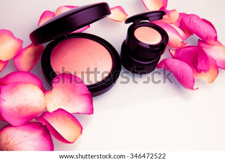 Makeup. Face powder and eye shadows isolated on white background with rose petals. Horizontal shot. - stock photo