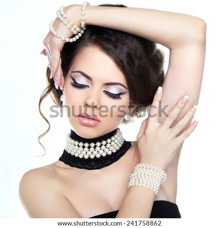 Makeup. Fashion beauty girl model posing in pearls jewelry isolated on white studio background