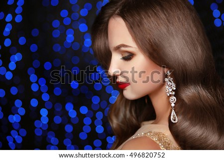 Makeup. Fashion earrings. Beautiful brunette elegant model with long wavy hair and jewelry  isolated on holiday blue party lights christmas background.