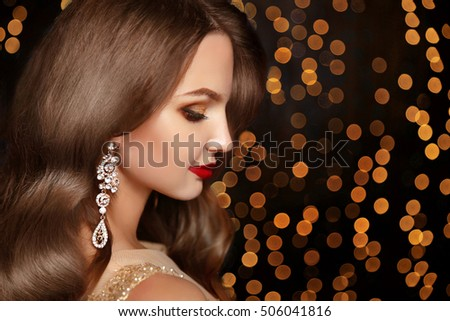 Makeup. Jewelry. Beautiful smiling woman model with expensive golden earrings, brunette long wavy hair and red lips over holiday party lights background.  Beauty studio portrait.