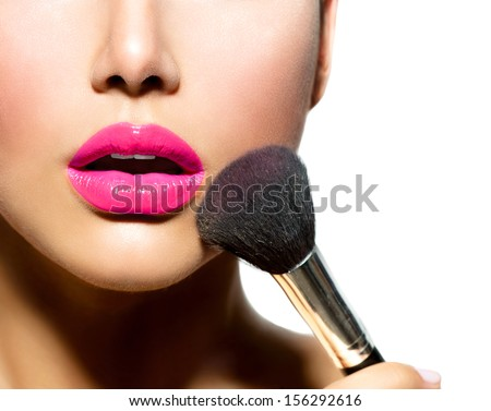 Makeup. Make-up Applying closeup. Cosmetic Powder Brush for Make up. Perfect Skin. Purple Lipstick. Isolated on a White Background. Makeover - stock photo