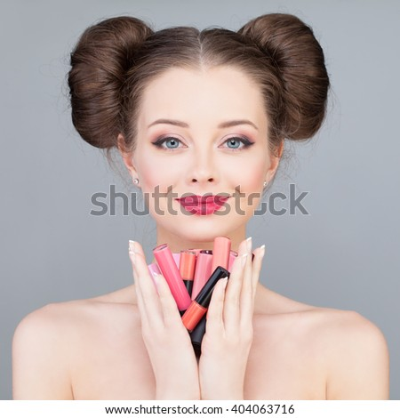 Makeup. Pretty Girl Holding Bright Lipsticks and Lipgloss - stock photo