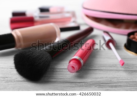 Makeup set with beautician, brush and cosmetics on white wooden  background