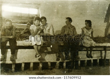 MAKHACHKALA, USSR - CIRCA 1950s: young people sitting on a feeding trough for the cows, laid by a straw, Makhachkala, Dagestan, USSR, 1950s