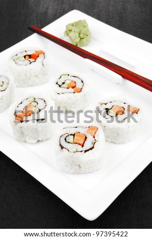 Maki Sushi - California Sushi Roll with Avocado, Cream Cheese and Raw Salmon inside. With wasabi . over black table - stock photo
