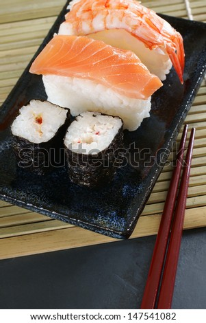 Maki sushi & nigiri sushi made with salmon and prawn on a Japanese ceramic dish with laquered chopsticks