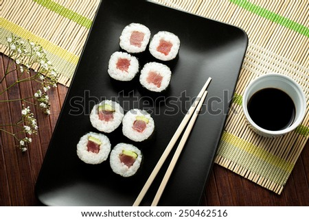 maki sushi on black plate with chopsticks - stock photo