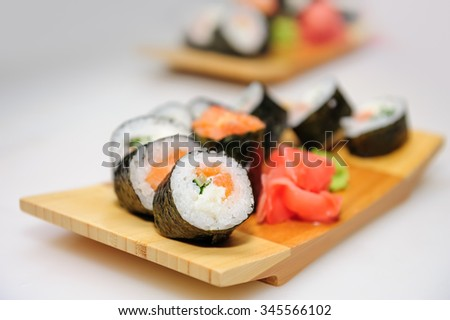 Maki sushi rolls set served on wooden board, closeup with selective focus, bokeh - stock photo