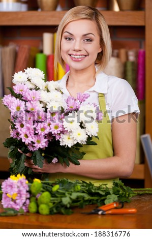 Making a beautiful flower bunch. Beautiful young blond hair woman in apron arranging flowers and looking at camera - stock photo