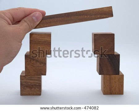 Making a bridge from toy wooden building blocks - stock photo