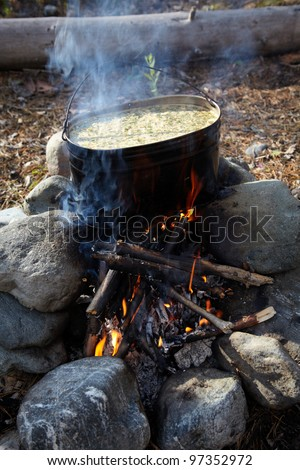 Making a food in a pot on campfire - stock photo