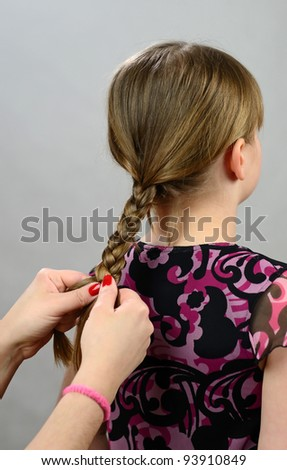 Making a hair braid for little girl - stock photo