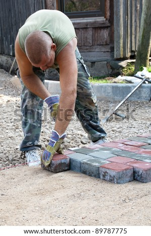 Making a pavement.Mason is building pavement. Hands in yellow gloves lays layers of bricks.