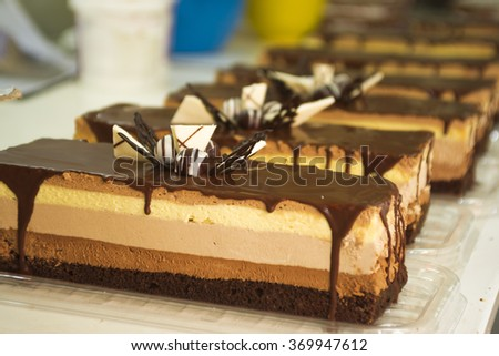 Making and row a chocolate cake on table, homemade work - stock photo