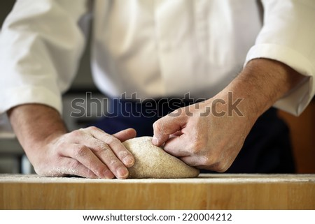 Making bread yeast dough, chef kneading in a bakery kitchen - stock photo