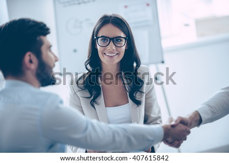 Making business. Close-up part of two men shaking hands while sitting on the couch at office with their beautiful coworker  - stock photo