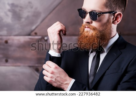 Making business look good. Close-up of a confident young man in shirt and tie adjusting his sleeves  - stock photo