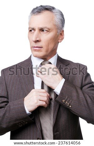 Making business look good. Confident mature man in formalwear adjusting his necktie and looking away while standing against white background - stock photo