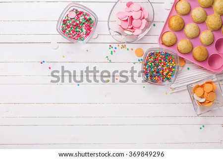 Making cake pops on white wooden background. Confetti  sprinkles. Selective focus.Place for text.