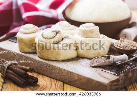 Making cinnamon buns. Homemade raw yeast dough after raising ready to bake, rustic style - stock photo