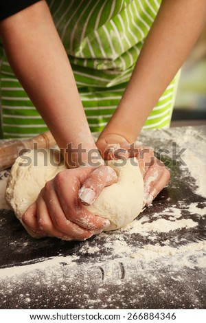 Making dough by female hands on wooden table and blurred  background - stock photo