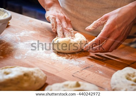 Making dough by female hands on wooden table background. preparing in bakery - stock photo