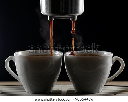 Making espresso coffee in two cups - stock photo