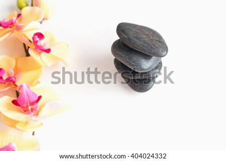 making for massage, with stones and flowers on a light background - stock photo