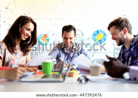 Making great decisions. Young beautiful woman gesturing and discussing something with smile while her coworkers listening to her sitting at the office table - stock photo