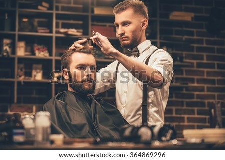 Making haircut look perfect. Young bearded man getting haircut by hairdresser while sitting in chair at barbershop - stock photo