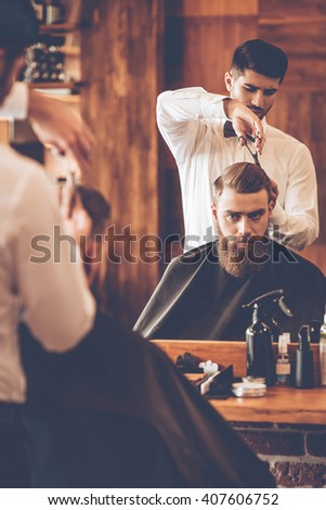 Making haircut look perfect. Young bearded man getting haircut by hairdresser while sitting in chair at barbershop in front of mirror