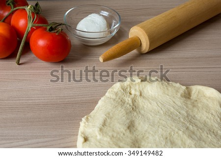 Making homemade original italian pizza , ingredients on wooden table - stock photo