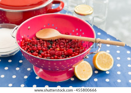 Making jam from redcurrants, raspberries and other red fruit - stock photo