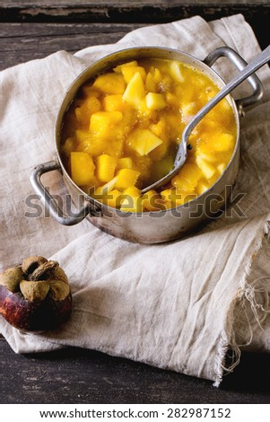 Making mango chutney or jam in vintage aluminum pan over old wooden table with whole and slice mangosteen. Dark rustic atmosphere - stock photo