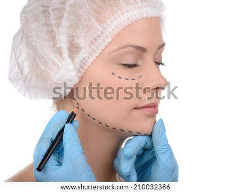 Making marks on face. Close-up of beautiful young woman in medical headwear keeping while doctors hands in gloves making marks on her face isolated on white - stock photo