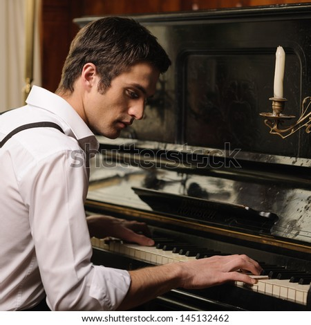 Making music. Profile of a handsome young men playing piano - stock photo