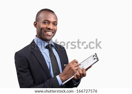 Making notes. Cheerful young African man in formalwear making notes in his note pad and smiling at camera while standing against white background - stock photo