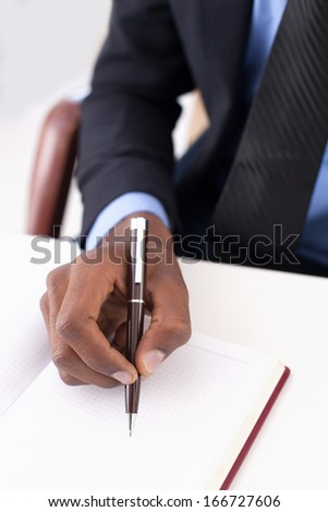 Making notes. Close-up of African businessman writing something in his note pad - stock photo