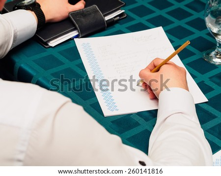 Making notes. Close-up of man in formalwear writing something in his note pad - stock photo